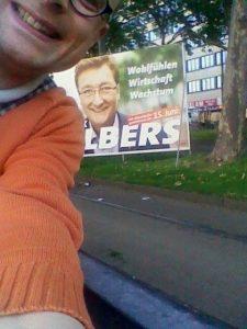 Dirk Elbers Zaun: Auch der Verfasser des Textes legt sich gern über den Zaun - hier in Düsseldorf vor einem Wahlplakat von Dirk Elbers.