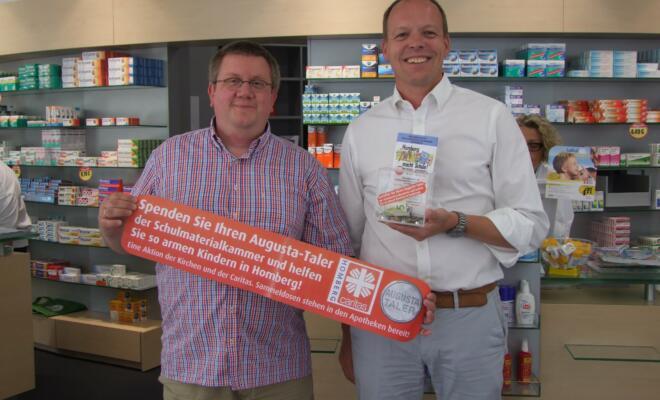 Beide hoffen auf viele Spenden: Apotheker Peter Vogt überreicht Diakon Stefan Ricken von der Gemeindecaritas die ersten gespendeten Taler.