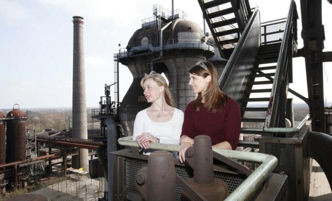 Isabella Vetter (Weinkönigin aus Baden, links) und ihre Amtskollegin Mara Walz aus Württemberg bestaunen die Aussicht vom Hochofen 5 des Landschaftspark Duisburg-Nord. Foto: Thomas Berns