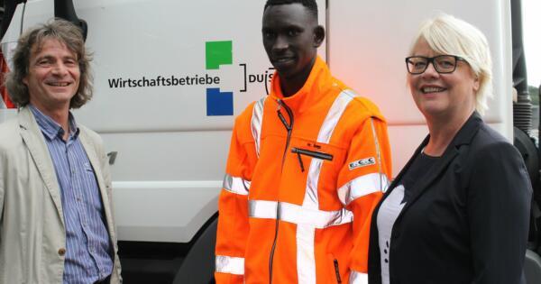Astrid Neese, Vorsitzende der Geschäftsführung der Agentur für Arbeit Duisburg (rechts) und Ludger Marker, Ausbilder Wirtschaftsbetriebe Duisburg (links) nehmen den Auszubildenden Saihou G. in ihre Mitte. (Foto: Wirtschaftsbetriebe Duisburg)